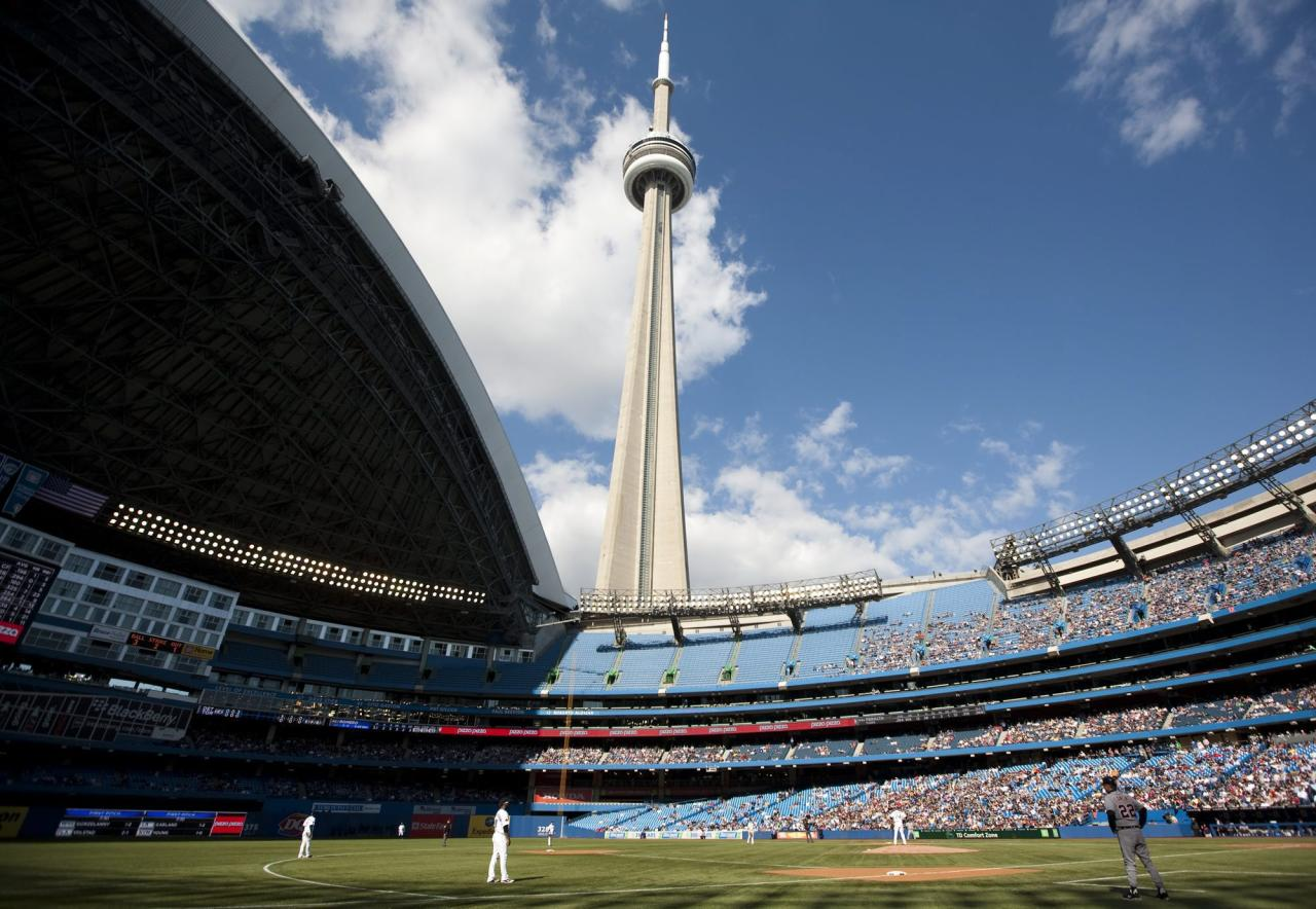 The CN Tower looms over the Toronto Blue Jays and Detroit Tigers as the Rogers Centre's roof is open for the first time in the 2011 MLB baseball season in Toronto Saturday, May 7, 2011. (AP Photo/The Canadian Press, Darren Calabrese)