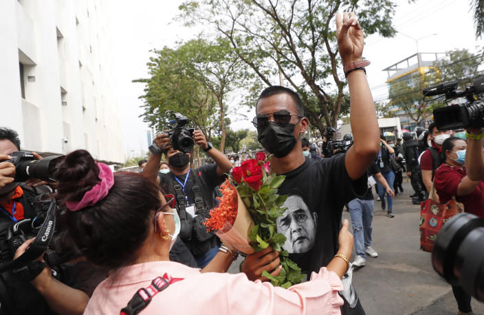 A pro-democracy activist, Panupong Jadnok, receives a flower from his supporter as he arrived at the Attorney General office in Bangkok, Thailand, Monday, March 8, 2021. Prosecutors in Thailand charged 18 pro-democracy activists with sedition on Monday, while lodging additional charges of insulting the monarchy against three of them. (AP Photo/Sakchai Lalit)