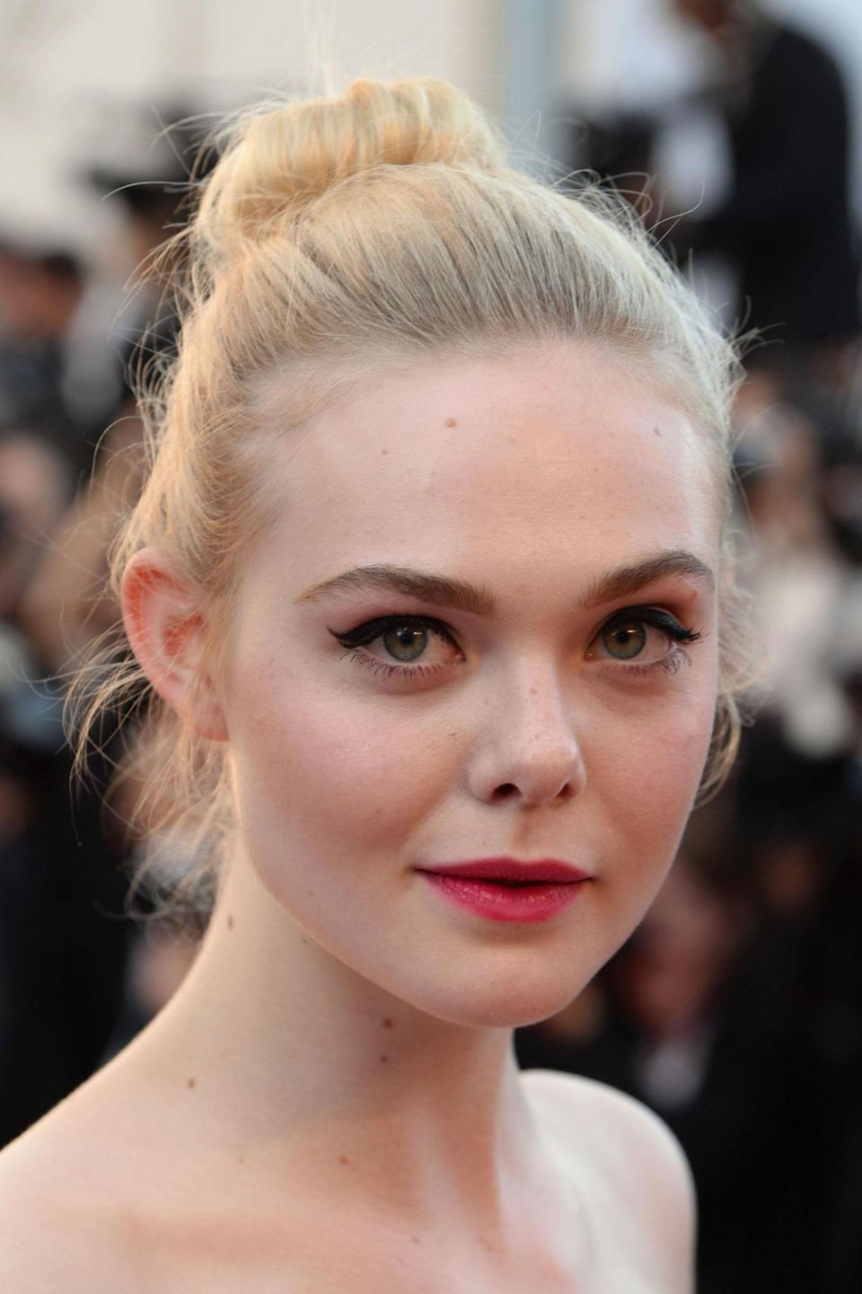 <p>L'Oreal Paris' latest recruit, Elle Fanning balanced her cute ballerina bun with vampy make-up; cate eyes and hot pink lips.</p>