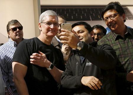 Apple CEO Tim Cook displays his Apple Watch while having a photograph taken by a customer in Palo Alto