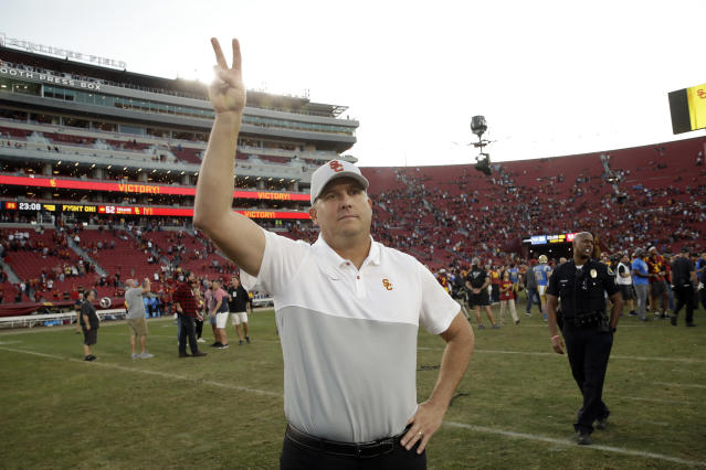 Southern California head coach Clay Helton signals to fans from midfield after a 52-35 win over UCLA in an NCAA college football game, Saturday, Nov. 23, 2019, in Los Angeles. (AP Photo/Marcio Jose Sanchez)