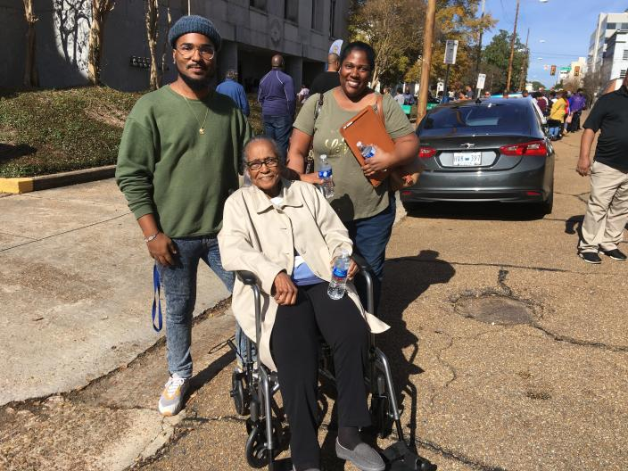 """Illinois Cox Littleton, 92, of Jackson, Miss., seated, went to the Hinds County Courthouse in Jackson on Saturday, Nov. 24, 2018, to cast an absentee ballot in a U.S. Senate runoff election. Littleton, a retired home economics teacher, says she voted for Democrat Mike Espy because she considers him """"a highly intelligent man."""" Littleton is accompanied by her grandson, Justin Austin, 25, and her daughter, Jacqueline Austin, 54, both of Jackson, Miss., who say they will cast ballots when polls are open Tuesday, Nov. 27, 2018. Espy is challenging Republican Sen. Cindy Hyde-Smith, who was appointed to serve in the Senate temporarily when longtime Republican Sen. Thad Cochran retired in April. (AP Photo/Emily Wagster Pettus)"""