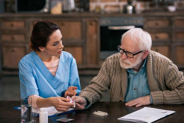 A young nurse sitting with an elderly patient discussing medication.