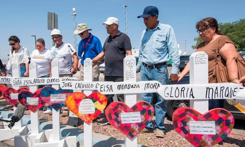 People pray beside crosses with the names of victims who died in the El Paso shooting.