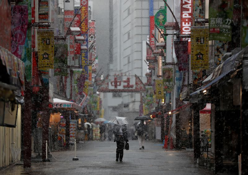 A man walks past on a nearly empty street in a snow fall during a coronavirus disease outbreak in Tokyo