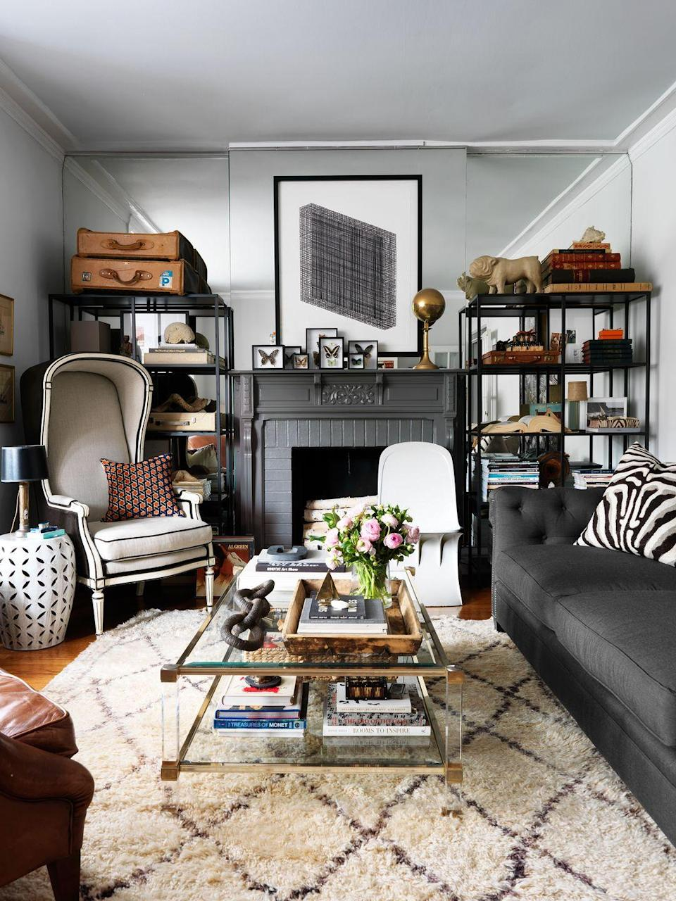 """<p>Interior designer Erik Kirk swapped out the old coffee table with one that includes a bottom shelf for more space to display decor and store collected items. Then, he added two shelving units against the back wall, which makes the room feel more complete while also giving them a place to stack all their books and keepsakes. </p><p><em><a href=""""https://www.housebeautiful.com/design-inspiration/house-tours/g15873332/devin-kirk-house-tour/"""" rel=""""nofollow noopener"""" target=""""_blank"""" data-ylk=""""slk:See more at House Beautiful »"""" class=""""link rapid-noclick-resp"""">See more at House Beautiful »</a> </em></p><p><strong>What you'll need:</strong> Wall shelving unit, $143, <a href=""""https://www.wayfair.com/furniture/pdp/gracie-oaks-theresa-tower-etagere-bookcase-grcs3182.html?piid="""" rel=""""nofollow noopener"""" target=""""_blank"""" data-ylk=""""slk:Wayfair.com"""" class=""""link rapid-noclick-resp"""">Wayfair.com</a></p>"""