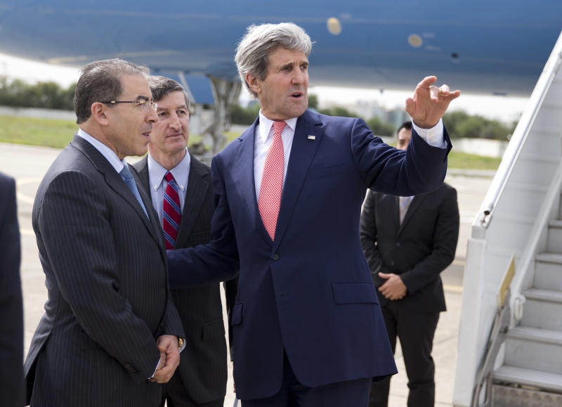 Secretary of State John Kerry, right, talks with Tunisian Foreign Minister Mongi Hamdi, left, and ambassador Jake Walles after arriving at El Aouina Air Base Tuesday, Feb. 18, 2014, in Tunis. Kerry is in Tunisia to offer continued American assistance for the North African nation where uprisings that toppled authoritarian leaders around the Arab world ignited in 2011. (AP Photo/ Evan Vucci, Pool)