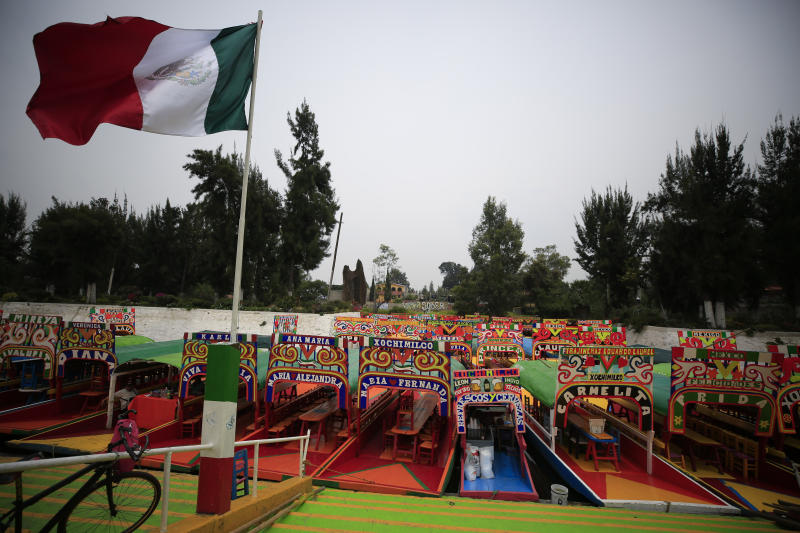 A Mexican flag flies over dozens of parked trajineras, the colorful passenger boats typically rented by tourists, families, and groups of young people, in Xochimilco, Mexico City, Friday, Sept. 6, 2019. The usually festive Nativitas pier was subdued and largely empty Friday afternoon, with some boat operators and vendors estimating that business was down by 80% on the first weekend following the drowning death of a youth that was captured on cellphone video and seen widely in Mexico. Borough officials stood on the pier to inform visitors of new regulations that went into effect Friday limiting the consumption of alcohol, prohibiting the use of speakers and instructing visitors to remain seated.(AP Photo/Rebecca Blackwell)