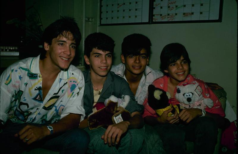 Ricky Martin posing next to Robi 'Draco' Rosa, holding a couple of stuffed animals.