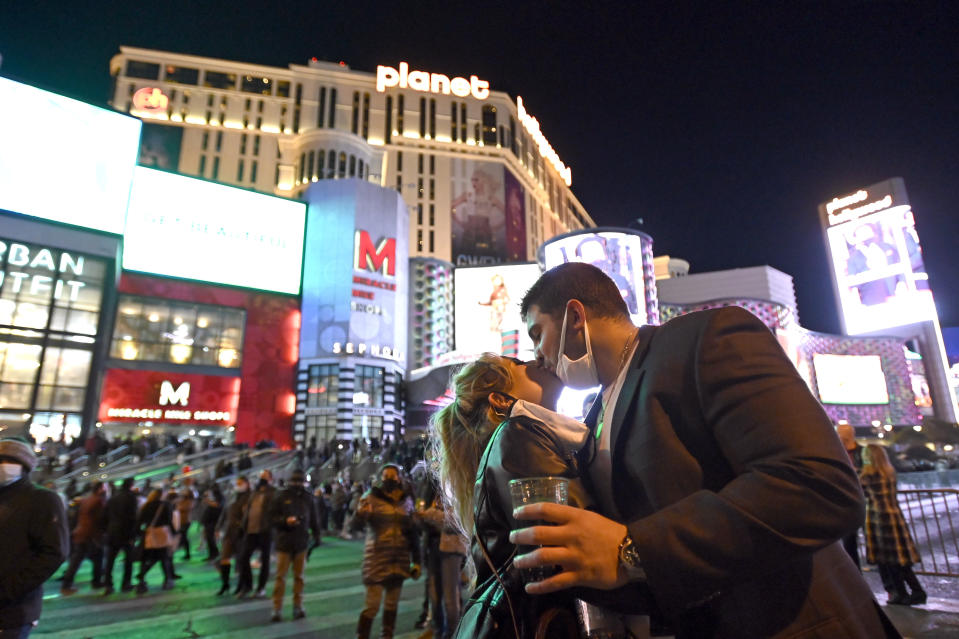 FILE - In this Dec 31, 2020, file photo, a couple kiss as they celebrate New Year's Eve along the Las Vegas Strip in Las Vegas. Thousands of New Year's revelers gathered beneath the neon-lit marquees on the Las Vegas Strip — even though the big annual fireworks show was called off due to the coronavirus pandemic. (AP Photo/David Becker, File)