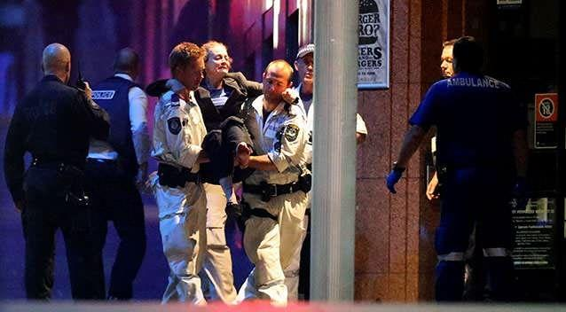 A hostage is carried from the Lindt cafe after Sydney's siege ends in tragedy. Photo: Getty