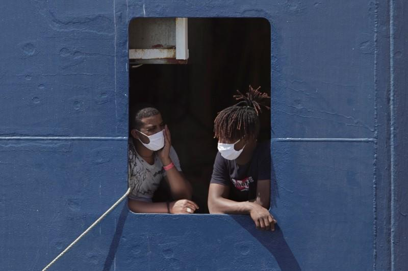 Migrants wait to disembark the ship 'Geo Barents' after week waiting at sea, in Augusta