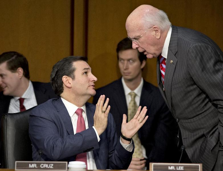 FILE - In this Jan. 30, 2013 file photo Senate Judiciary Committee member Sen. Ted Cruz, R-Texas, left, talks with committee Chairman Patrick Leahy, D-Vt., during a hearing about gun violence on Capitol Hill in Washington. Weeks into his job, Texas Republicans are cheering Cruz's indelicate debut and embracing him as one of their own. The insurgent Republican elected with the tea party's blessing and bankroll, has run afoul of GOP mainstays, prompted Democrats to compare his style to McCarthyism. (AP Photo/J. Scott Applewhite, File)
