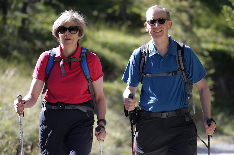 British Prime Minister Theresa May (L) walks in a forest with her husband Philip (R) at the start of a summer holiday in the Alps in Switzerland on August 12, 2016. / AFP / POOL / MARCO BERTORELLO (Photo credit should read MARCO BERTORELLO/AFP/Getty Images)