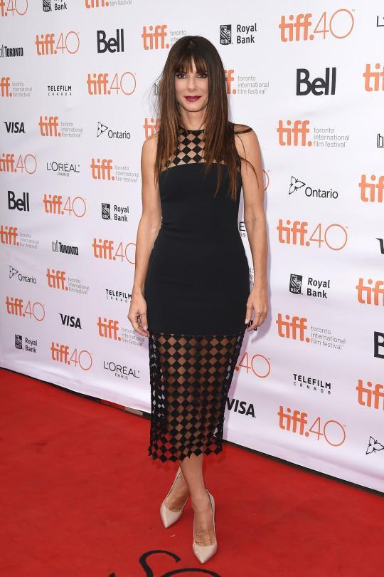 <p>After taking a break from the red carpet for a year, having Sandra Bullock back is cause for celebration and the actress dressed ready to do just that. In a black David Koma dress with patterend sheer at the shoulders and hemline, Bullock attended the premiere of her new film 'Our Brand is Crisis' during the 2015 Toronto International Film Festival.</p>