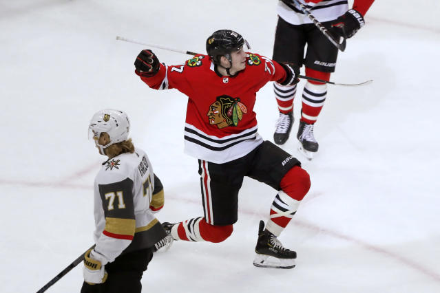 Chicago Blackhawks' Kirby Dach (77) celebrates his first NHL goal as Vegas Golden Knights' William Karlsson (71) skates by during the first period of a hockey game Tuesday, Oct. 22, 2019, in Chicago. (AP Photo/Charles Rex Arbogast)
