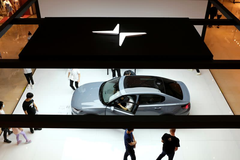 People look at a Polestar 2 electric sedan displayed in a shopping mall in Shanghai