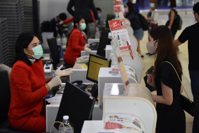 BANGKOK, THAILAND - MAY 01, 2020: A staff of Air Asia airline speaks with a passenger while wearing a face mask and gloves as a preventive measure at Don Muang International Airport during the Coronavirus (COVID-19) crisis. Low cost airline resuming its domestic operations from 1 May 2020 in service for passengers in need of travel. After flying was temporarily closed due to Covid-19 pandemic.- PHOTOGRAPH BY Yuttachai Kongprasert / Echoes Wire / Barcroft Studios / Future Publishing (Photo credit should read Yuttachai Kongprasert / Echoes Wire/Barcroft Media via Getty Images)