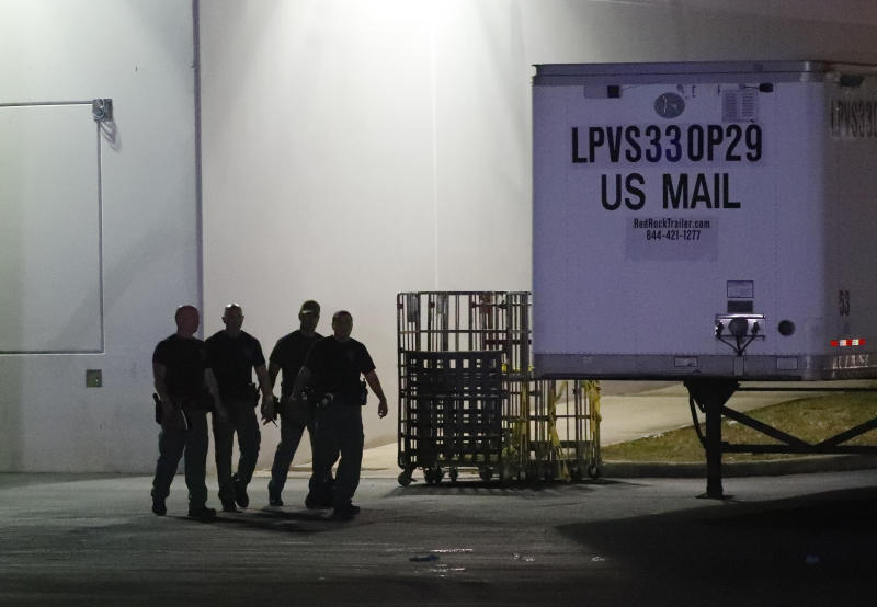 Members of the Miami Dade County Bomb Squad walk outside a postal facility in Opa-locka Fla. late Thursday night. More