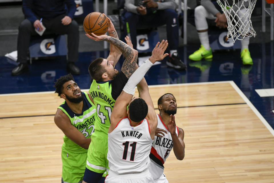 Minnesota Timberwolves forward Juancho Hernangomez (41) shoots over Portland Trail Blazers center Enes Kanter (11) and guard Rodney Hood, right, as Timberwolves center Karl-Anthony Towns (32) watches during the first half of an NBA basketball game Saturday, March 13, 2021, in Minneapolis. (AP Photo/Craig Lassig)
