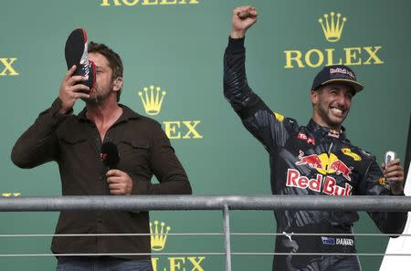 Formula One F1 - U.S. Grand Prix - Circuit of the Americas, Austin, Texas, U.S., 23/10/16. Third placed finisher Red Bull driver Daniel Ricciardo of Australia celebrates as actor Gerard Butler drinks Red Bull from Ricciardo's racing shoe during the ceremony after the race.    REUTERS/Adrees Latif