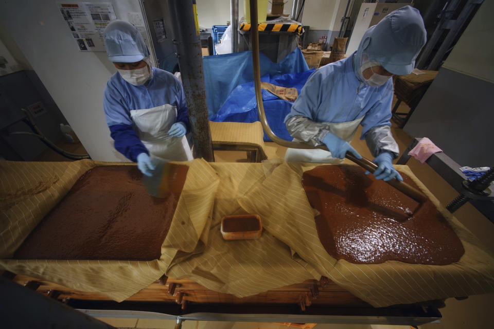 Workers of Yagisawa Shoten Co., prepare for soy sauce extractor of the company's factory in Ichinoseki, Iwate Prefecture, northeastern Japan Friday, March 5, 2021. Just a month after a tsunami smashed into the city of Rikuzentakata, soy sauce maker Michihiro Kono inherited his family's two-century-old business from his father. Later this year the ninth generation owner of Yagisawa Shoten Co. will open a new factory on the same ground where his family started making soy sauce in 1807. (AP Photo/Eugene Hoshiko)