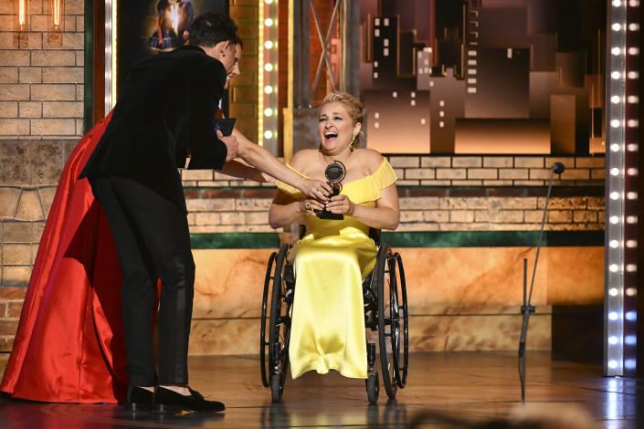 """Laura Benanti, from left, and Anthony Ramos present the award for best performance by an actress in a featured role in a musical to Ali Stroker for her performance in """"Rodgers & Hammerstein's Oklahoma!"""" at the 73rd annual Tony Awards at Radio City Music Hall on Sunday, June 9, 2019, in New York. (Photo by Charles Sykes/Invision/AP)"""