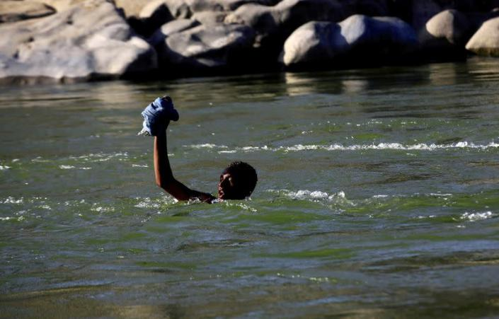 FILE PHOTO: An Ethiopian fleeing fighting in Tigray region lifts his clothes as he crosses the Setit river on the Sudan-Ethiopia border in Hamdayet village in eastern Kassala state