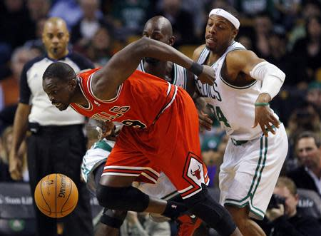 Chicago Bulls forward Luol Deng (L) breaks through the defense of Boston Celtics forwards Kevin Garnett (rear) and Paul Pierce (R) in the first quarter of their NBA basketball game in Boston, Massachusetts February 13, 2013. REUTERS/Brian Snyder