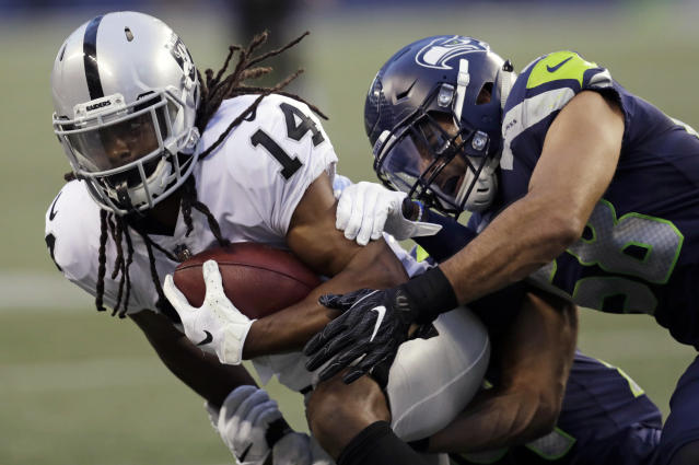 Oakland Raiders wide receiver Keon Hatcher (14) is tackled by Seattle Seahawks linebacker Austin Calitro, right, during the first half of an NFL football preseason game, Thursday, Aug. 30, 2018, in Seattle. (AP Photo/Stephen Brashear)