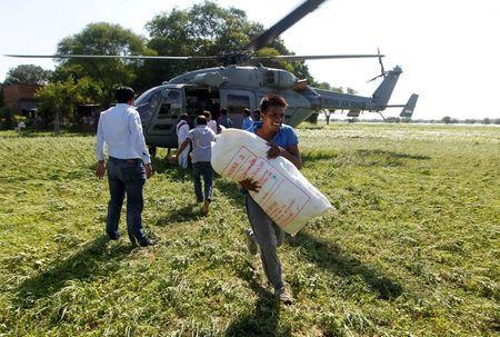 A man unloads relief food material from an Indian Air Force helicopter to be distributed among the flood victims, on the outskirts of Allahabad, India, August 24, 2016. REUTERS/Jitendra Prakash