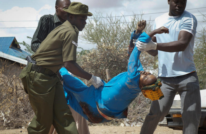 Members of the Kenyan security forces remove the body of a woman killed in the attack at the African Inland Church in Garissa, Kenya Sunday, July 1, 2012. Grenade and gunfire attacks on two Kenyan churches near the border with Somalia killed 10 people and wounded 40 on Sunday in what was likely an attack by militants from Somalia, an official said. (AP Photo/Chris Mann)