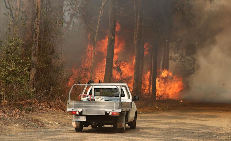 A ute is seen in front of a bushfire burning next to Busby's Flat Road in Busbys Flat, in northern NSW.