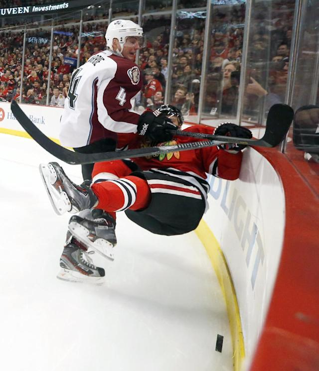 Colorado Avalanche defenseman Tyson Barrie (4) checks Chicago Blackhawks right wing Kris Versteeg along the boards during the second period of an NHL hockey game Friday, Dec. 27, 2013, in Chicago. (AP Photo/Charles Rex Arbogast)