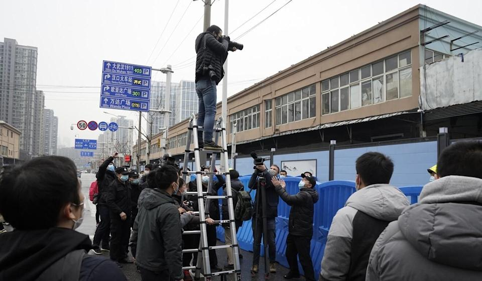 Journalists outside the Huanan Seafood Market. Photo: AP