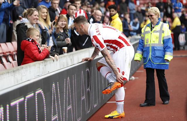 <p>Stoke City's Marko Arnautovic gives his boots to a young fan after the game </p>
