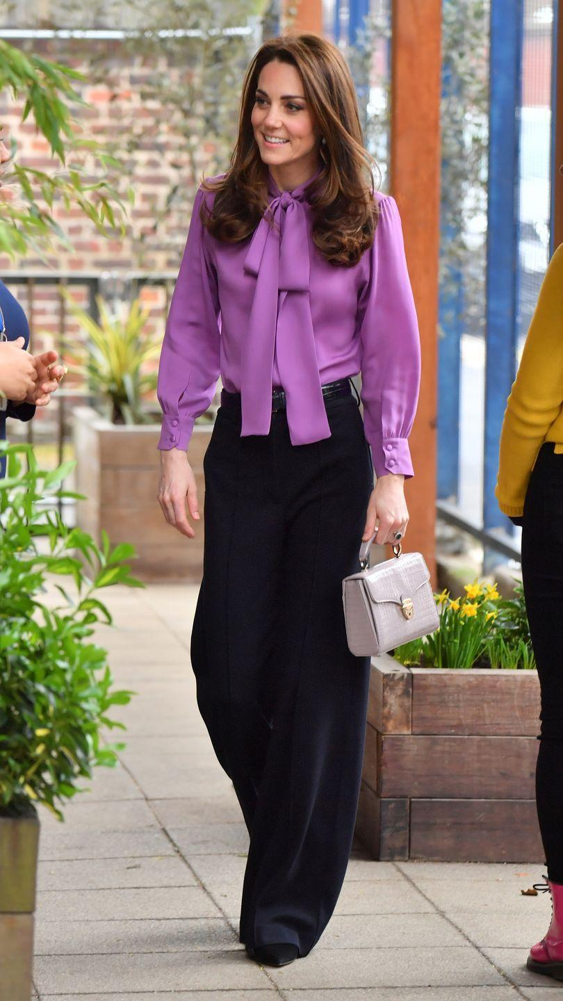 <p>The Duchess chose a wide-legged trouser paired with a purple pussybow blouse for her visit to the Henry Fawcett Children's Centre. She paired the look with a small top-handled bag and black pumps.</p>