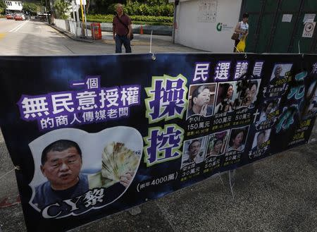 A poster mocking Jimmy Lai Chee-ying, chairman of Next Media, offering money to pro-democracy lawmakers, is displayed at Hong Kong's financial Central district August 29, 2014. REUTERS/Bobby Yip
