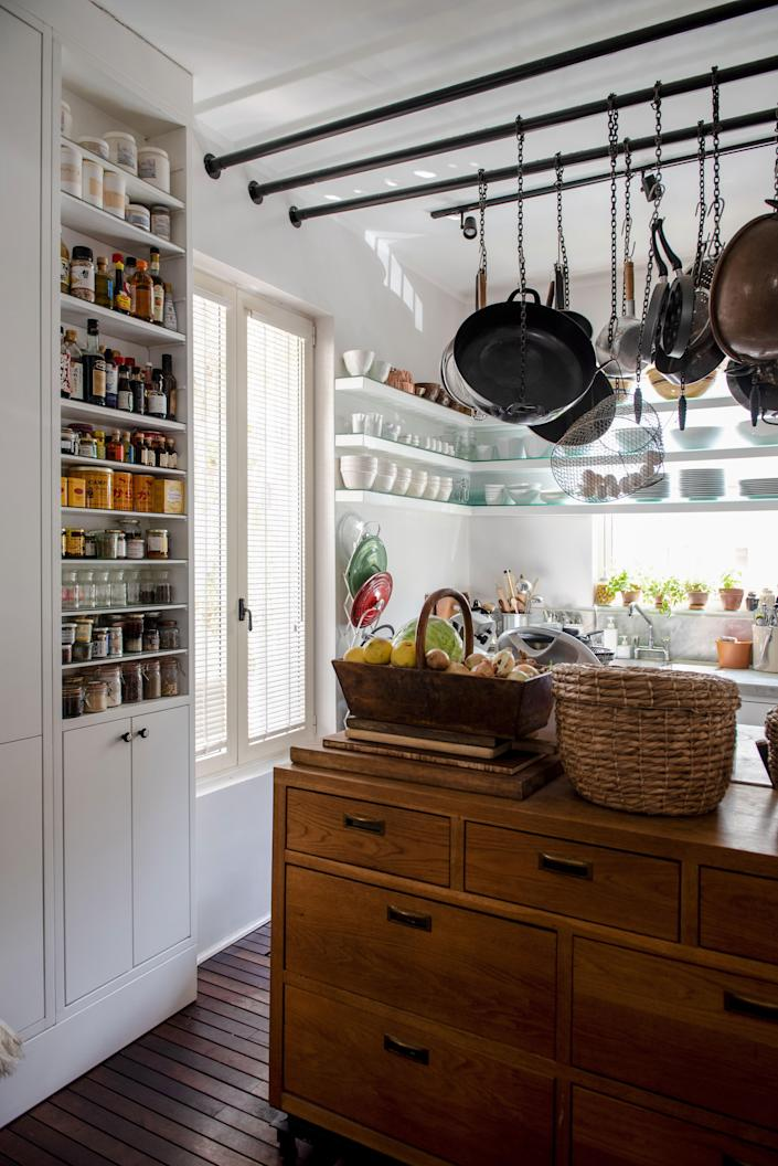 Every facet of the couple's kitchen was crafted by a local carpenter. The cabinets are painted in white oil and the chest of drawers is made of pure oak; a mix of custom-designed rods and chains suspend various pots and pans in the air, making for easy access.