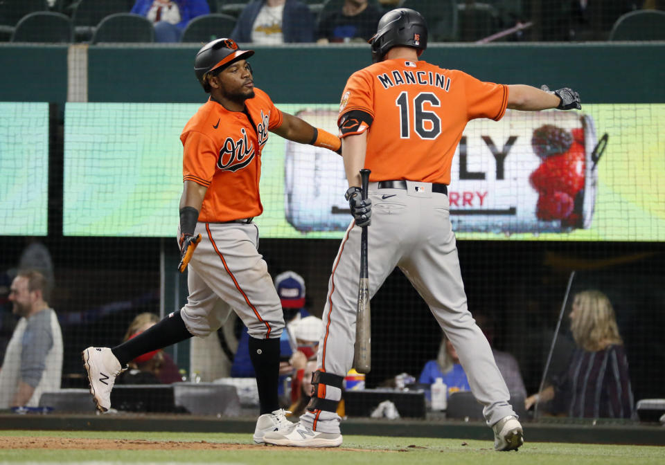 Baltimore Orioles' Maikel Franco, left, slaps hands with Trey Mancini after hitting a two-run home run against the Texas Rangers during the ninth inning of a baseball game in Arlington, Texas, Saturday, April 17, 2021. (AP Photo/Ray Carlin)