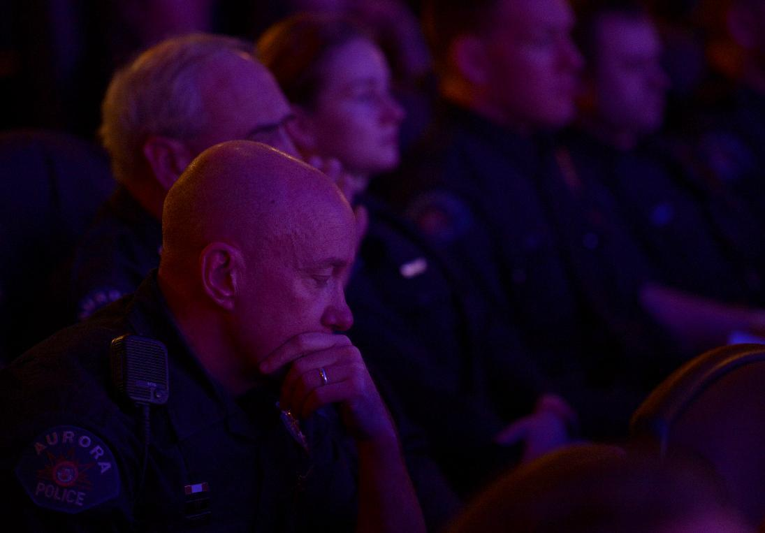 Aurora Police Officer Mike Hawkins, a 18 year veteran and first responder to the shooting sits with other Aurora Police officers during the reopening and remembrance ceremony at the Century Aurora cinema, formerly the Century 16, Thursday, Jan. 17, 2013 in Aurora, Colo. The cinema is where 12 people were killed and dozens injured in a shooting rampage last July. (AP Photo/The Denver Post, RJ Sangosti, Pool)