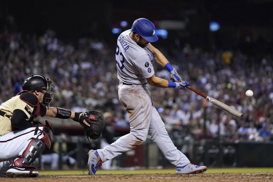 Los Angeles Dodgers' Steven Souza connects for a home run next to Arizona Diamondbacks catcher Carson Kelly during the eighth inning of a baseball game Friday, June 18, 2021, in Phoenix. (AP Photo/Ross D. Franklin)