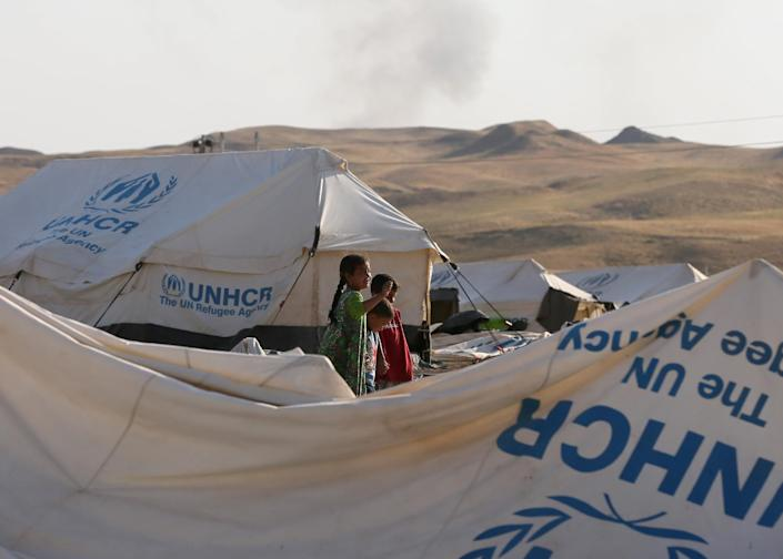 Children stand near tents at a camp for displaced Iraqi Shiite Turkmen in Shikhan, in Kurdistan's Dohuk province, on June 24, 2014 (AFP Photo/Karim Sahib)