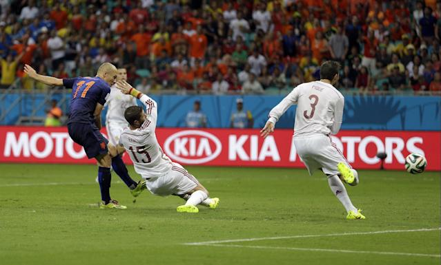 FILE - In this June 13, 2014 file photo, Netherlands' Arjen Robben kicks past Spain's Sergio Ramos (15) and Gerard Pique to score his side's second goal during the second half of the group B World Cup soccer match at the Arena Ponte Nova in Salvador, Brazil. Robben had already scored one goal in the rout over Spain, but his second was done with awe-inspiring speed. (AP Photo/Natacha Pisarenko, File)