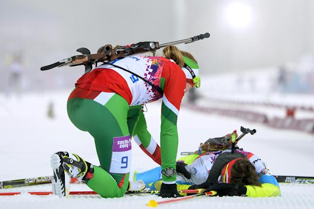 SOCHI, RUSSIA - FEBRUARY 11: Darya Domracheva of Belarus (L) reaches out to Teja Gregorin of Slovenia at the finish line in the Women's 10 km Pursuit during day four of the Sochi 2014 Winter Olympics at Laura Cross-country Ski & Biathlon Center on February 11, 2014 in Sochi, Russia. (Photo by Harry How/Getty Images)