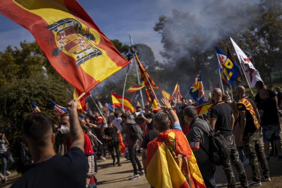A man makes the fascist salute as others wave preconstitutional flags as ultra right wing protesters march during an alternative celebration for Spain's National Day in Barcelona, Spain, Tuesday, Oct. 12, 2021. Spain commemorates Christopher Columbus' arrival in the New World and also Spain's armed forces day. (AP Photo/Emilio Morenatti)