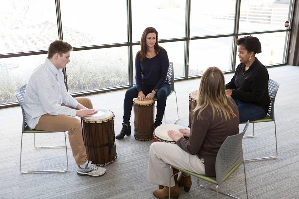 Joan Kleinmann, center, leads a group at HopeWay through a music therapy program with drums.