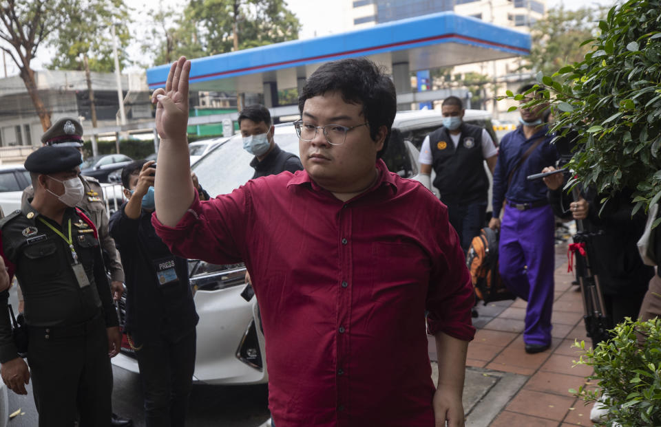 Thai activist Parit Chiwarak, raise a three-fingers salute, a symbol of resistance arrive at Criminal court in Bangkok, Thailand, Tuesday, Feb. 9, 2021. Four activists, including Parit, from Thailand's prodemocracy movement reported themselves to the court on Tuesday as they are formally charge of defaming the monarchy, as the authorities step up legal actions against protesters accused of insulting the royal institution. (AP Photo/Sakchai Lalit)