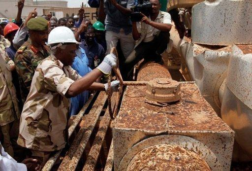 Sudanese Oil Minister Awad Ahmad al-Jaz turns the tap to start pumping oil from the war-damaged Heglig oil facility