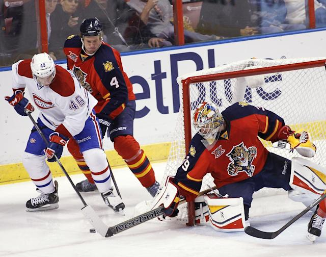 Montreal Canadiens left wing Michael Bournival (49) shoots as Florida Panthers' Dylan Olsen (4) and goalie Dan Ellis (39) defend during the second period of an NHL hockey game in Sunrise, Fla., on Saturday, March 29, 2014. (AP Photo/Terry Renna)